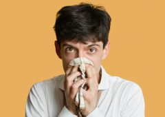 Portrait of a young man blowing nose over colored background